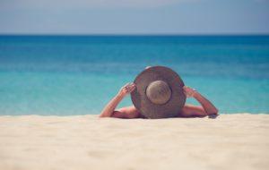 donna ri rilassa distesa in spiaggia