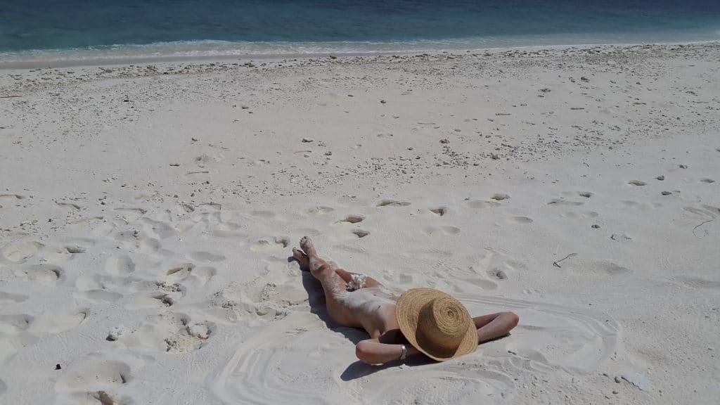 donna prende il sole su una spiaggia naturista