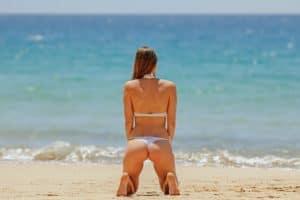 donna in bikini in spiaggia davanti al mare