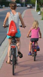 mamma e figlia pedalano in bici su pista ciclabile